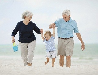 grandparents and child in sand - 320x246